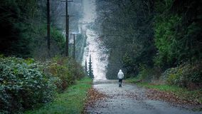 man-walking-down-hill-road-distance-wide-shot-wooded-hillside-cars-passing-nearby-81464531